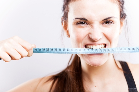 Angry young woman biting measuring tape Stock Photo