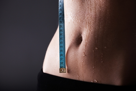 Fitness woman sweaty sporty belly after exercise with measuring tape