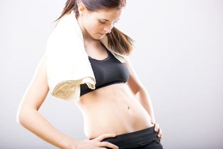 Young woman looking at her flat stomach after training with towel photo