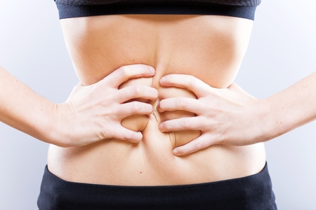 clutching: Hands of woman with stomach clutching her belly Stock Photo