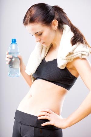flat stomach: Giovane donna guardando il suo ventre piatto con un asciugamano e una bottiglia d'acqua Archivio Fotografico