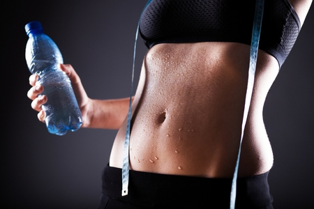 Fitness woman wet sporty belly after exercise with measuring tape and water bottle Stock Photo