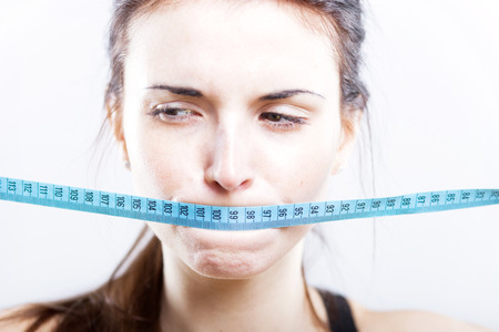 Woman with measuring tape covering her mouth, weight loss concept