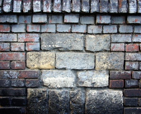 uncoated: Old stone wall filled with bricks, texture