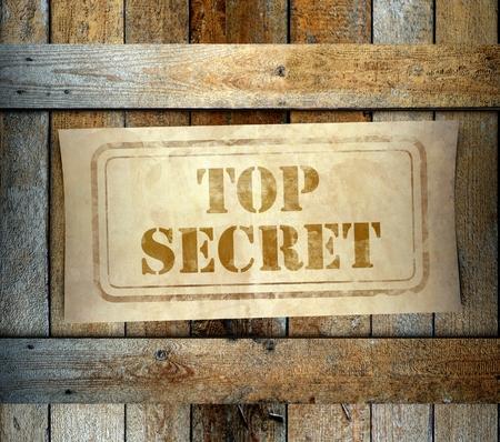 Stamp Top Secret label on old wooden box photo