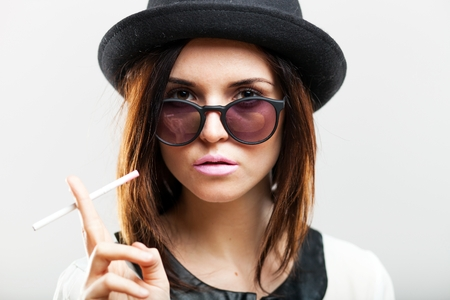 Retro fashion portrait of stylish young woman with cigarette photo