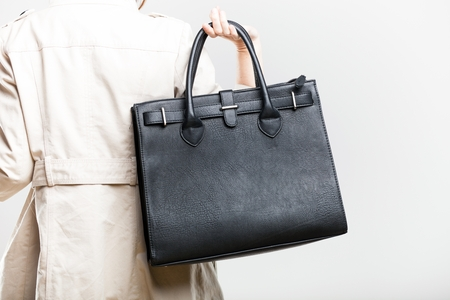 handbag: Elegant woman in white coat holding black bag, back view