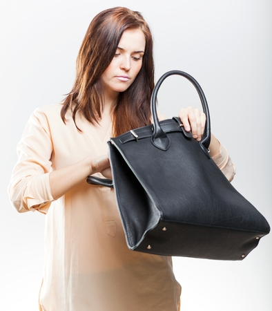 Elegant young woman looking in her black leather bag photo