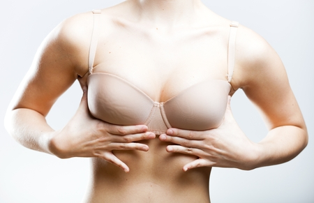Woman pushing up her breasts holding hands on bra photo