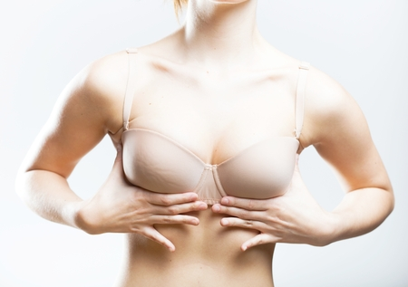 Women holding her hands on the bra cups and pushing them up photo