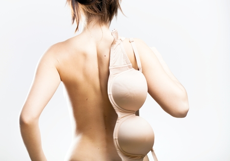 Bra hanging on woman back, symbol of temptation