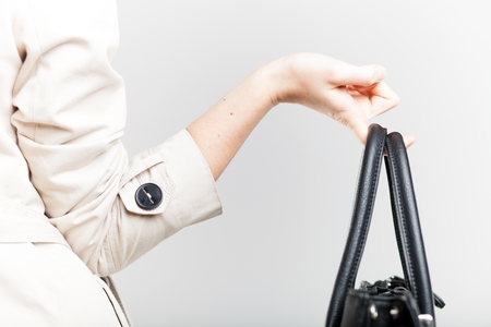 Elegant woman in white coat holding on finger black bag, back view photo