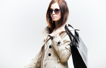 Elegant woman in white coat with black leather bag photo