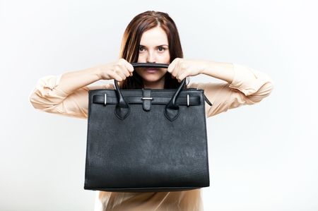 Elegant young woman holding black leather bag photo