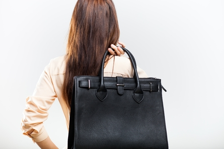 Elegant young woman with black leather bag, back view photo