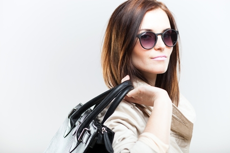 Fashionable woman in white coat with black bag and sunglasses photo