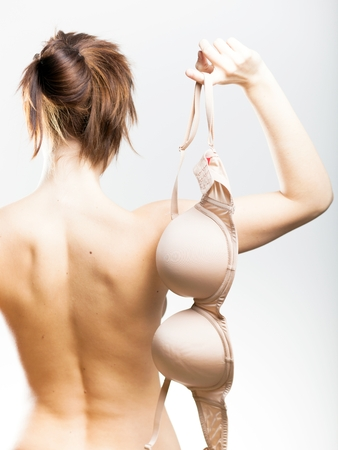 Naked woman back view holding bra in her hand photo
