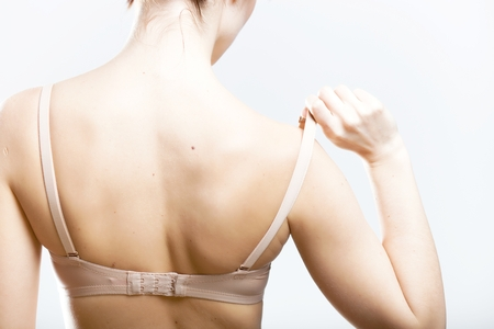 Woman holding a skin colored bra strap, closeup back view photo