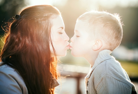 Young mother kissing child outdoor, love and affection photo