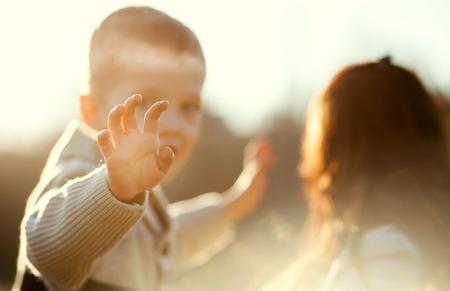 despedida: Agitando la mano del niño, niño pequeño con la madre al aire libre