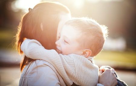hugging: Mother hugging her child druing walk in the park