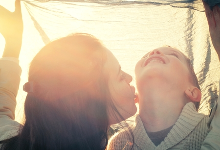 Mother kissing her child druing playing outdoor photo
