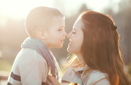 Young mother kissing child outdoor, love and affection