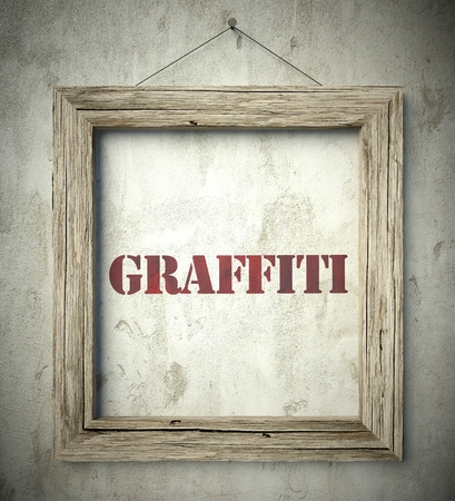 scraping: Graffiti emblem in old wooden frame on aged wall Stock Photo