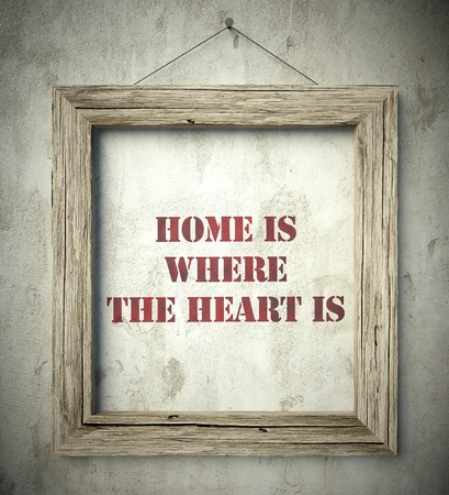Home is where the heart is in old wooden frame on aged wall photo
