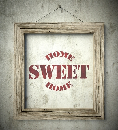 old home: Home sweet home emblem in old wooden frame on aged wall Stock Photo