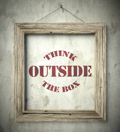 Think outside the box in old wooden frame on aged wall photo