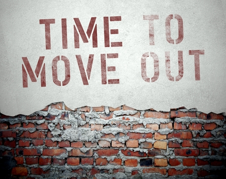 Time to move out concept on old brick wall background photo