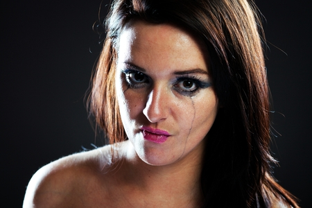 smeared mascara: Angry and hurt woman crying, face with smeared make up on dark background Stock Photo