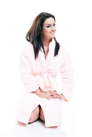 house robe: Full length portrait of woman sitting in bathrobe isolated white