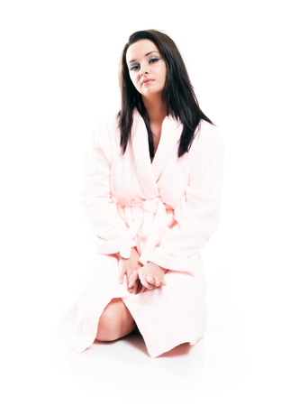 Full length portrait of woman sitting in bathrobe isolated white photo