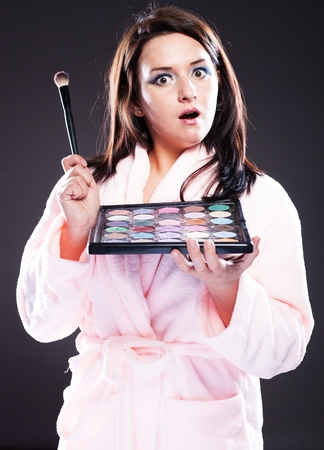 house robes: Funny surprised woman in bathrobe and make up palette Stock Photo