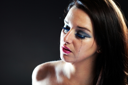 Hurt woman crying, face with smeared make up on dark background photo