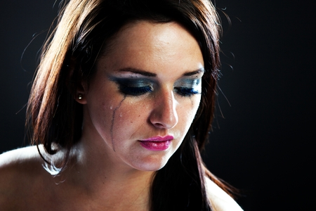 Hurt woman crying, face with smeared make up on dark background Stock Photo - 28211568