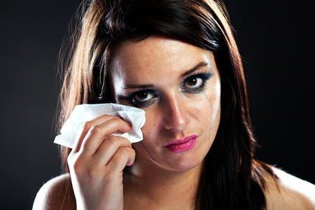 Hurt woman crying, face with smeared make up on dark background Stock Photo