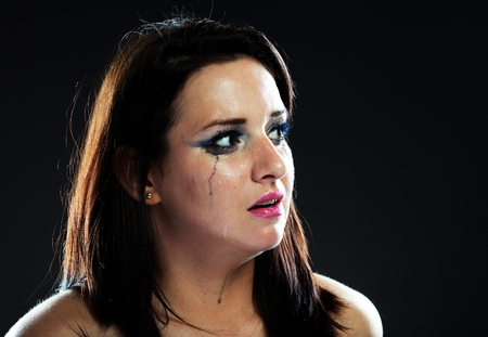 smeared: Hurt woman crying, face with smeared make up on dark background Stock Photo