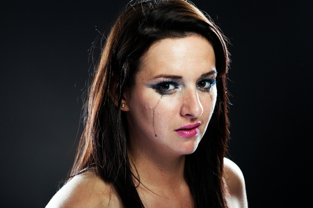 Hurt woman crying, face with smeared make up on dark background Stock Photo - 28211601