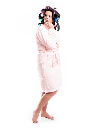 Thinking woman in bathrobe and hair with curlers, full length portrait isolated white photo