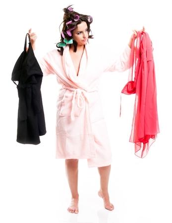 isolated  white: Donna in accappatoio sceglie i vestiti, piena lunghezza ritratto isolato bianco Archivio Fotografico