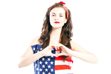 Pin up girl wrapped in american flag with hand in heart form isolated white photo
