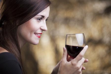 jovenes tomando alcohol: La mujer del encanto elegante en el restaurante con un vaso de vino tinto
