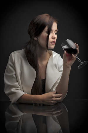 Glamour portrait of a woman with glass of red wine photo
