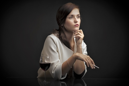 Glamour portrait of a woman with glass of red wine and cigarette photo