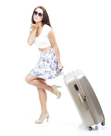 Tourist woman with suitcase sending kiss isolated white photo