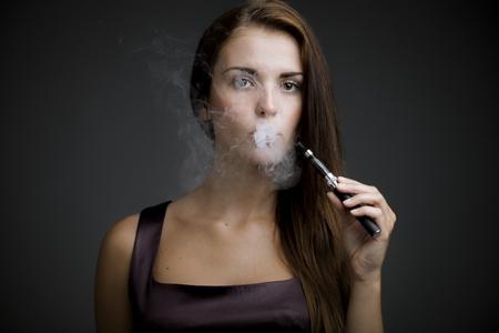 Femme élégante de fumer e-cigarette avec de la fumée portrait Banque d'images - 30769217