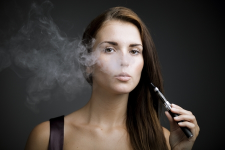 mujer elegante: Mujer elegante de fumar cigarrillo electr�nico con el retrato de humo